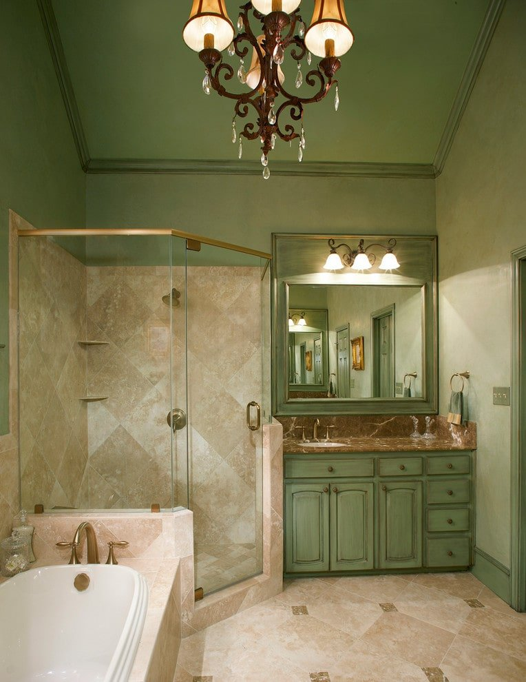 This primary bathroom is illuminated by a classic chandelier and glass sconces mounted above the chrome framed mirror. It has a drop-in tub and a walk-in shower along with a green vanity that blends in with the walls and vaulted ceiling.