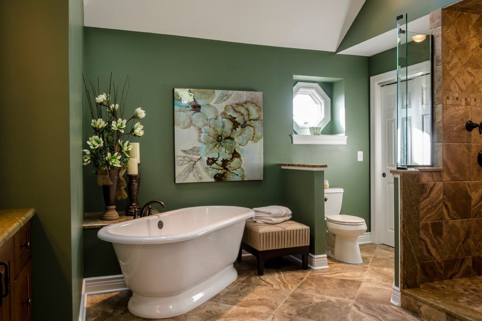 A lovely floral artwork hangs above the freestanding tub and cushioned stool over beige tiled flooring. This room showcases a walk-in shower and a toilet area under an octagonal window that's fitted on an inset wall niche.