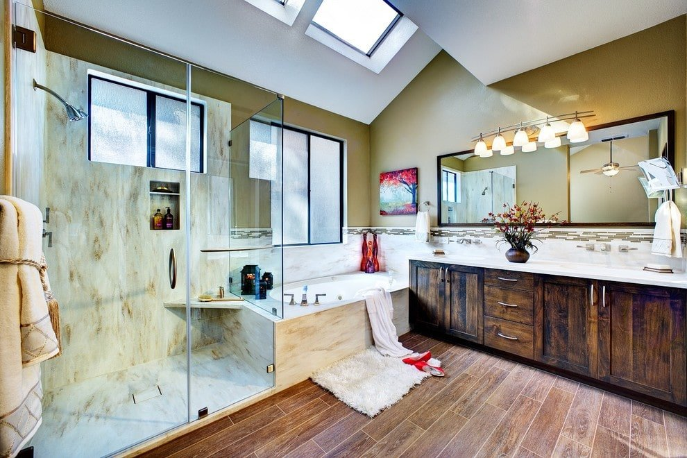 Cozy master bathroom with a walk-in shower and a deep soaking tub accented by a gorgeous painting that's mounted on the moss green wall. It includes a rustic vanity illuminated by glass sconces along with natural light from the glazed windows and skylights.