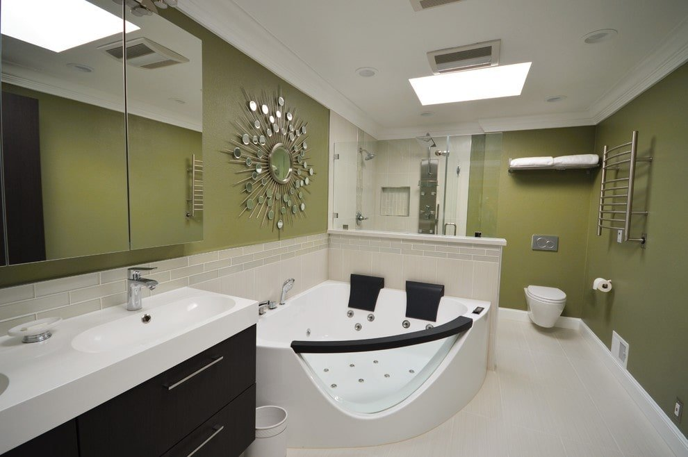 A gorgeous sunburst mirror adds a nice accent in this primary bathroom with a whirlpool tub and a black vanity paired with a mirrored medicine cabinet. It includes a modern wall hung toilet and a walk-in shower fitted with chrome fixtures.