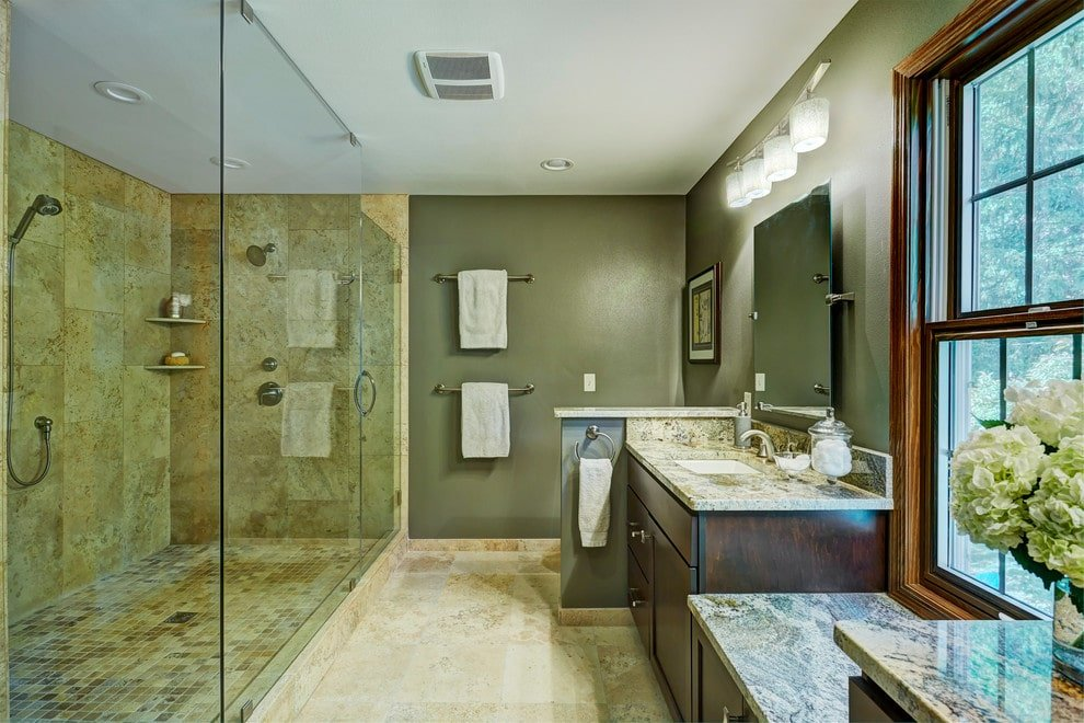 The green master bathroom features a large walk-in shower facing the dual sink vanity and a small toilet area under a lovely artwork. It has limestone flooring and a wooden framed window inviting natural light in.