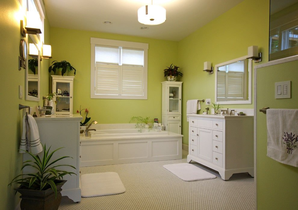 Green potted plants create a refreshing ambiance in this primary bathroom with facing sink vanities and a deep soaking tub flanked by sleek cabinets. It has lime green walls and hex tile flooring topped by white rugs.