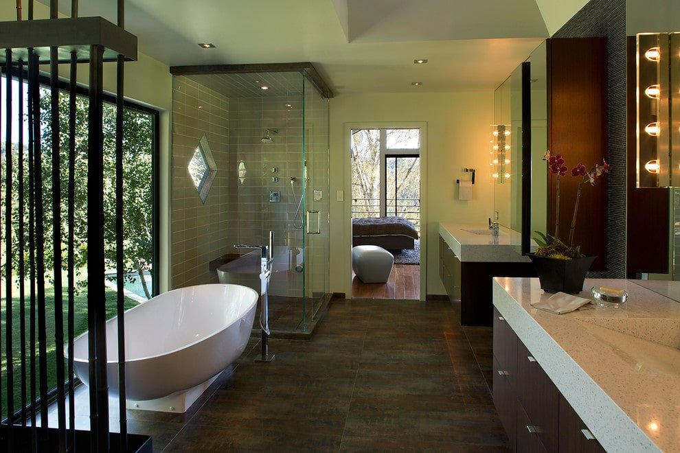 Linear glass sconces illuminate the floating sink vanities in this primary bathroom with distressed flooring and a panoramic window overlooking the lush green outdoor.