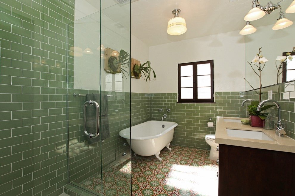 Fresh master bathroom offers a clawfoot tub and a toilet that sits next to the dual sink vanity paired with a frameless mirror. It has decorative tile flooring and white walls dominated by green subway tiles.