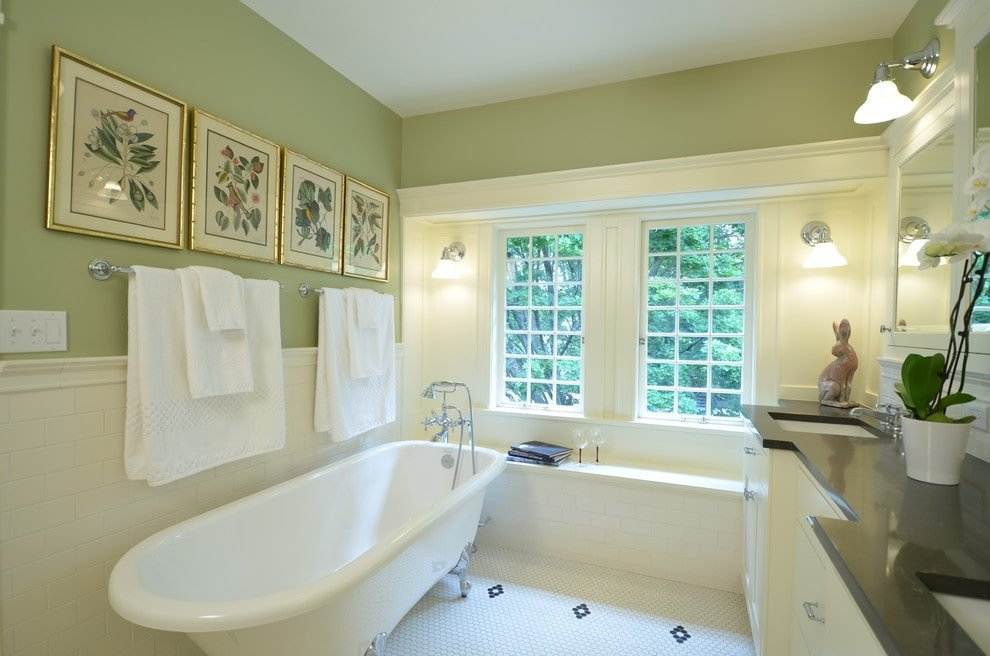 Bright primary bathroom designed with brass framed wall arts mounted above the chrome towel racks. It features a clawfoot tub and a white vanity contrasted by an absolute granite countertop.
