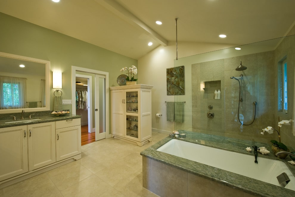 A white cabinet faces the sink vanity that's topped with a green granite countertop. It is accompanied by a deep soaking tub and a walk-in shower lighted by recessed ceiling lights.