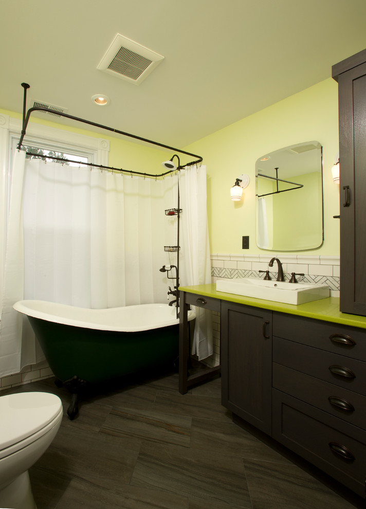 Glass sconces flank a frameless mirror that hung above the dark wood vanity topped with a green countertop and vessel sink. It is accompanied by a toilet and a black clawfoot tub that's integrated with a shower.
