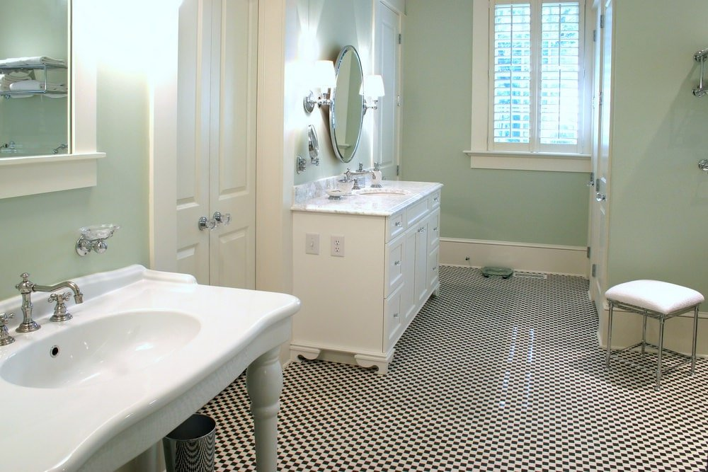 Black and white checkered flooring adds a striking contrast to the sage green walls in this primary bathroom with a porcelain washstand and white vanity under a round mirror flanked by chrome sconces.
