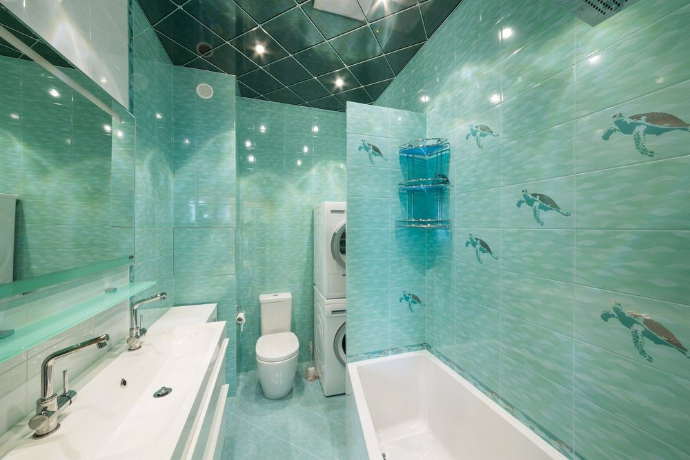 This primary bathroom boasts a long sink vanity and a drop-in bathtub along with a toilet and laundry area. It has a stylish mirrored ceiling and green tiled walls designed with sea turtles.