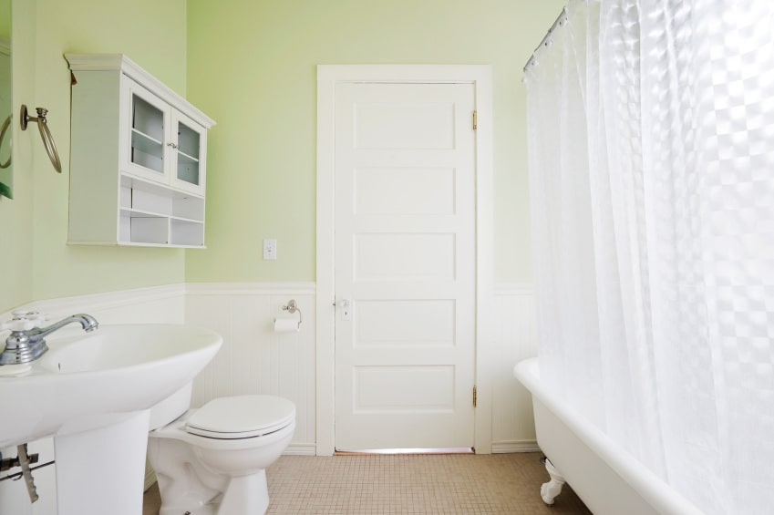 A floating cabinet is fixed above the toilet that's accompanied by a pedestal sink along with a shower and tub combo enclosed in a white checkered curtain. It is surrounded by green walls clad in white beadboard.