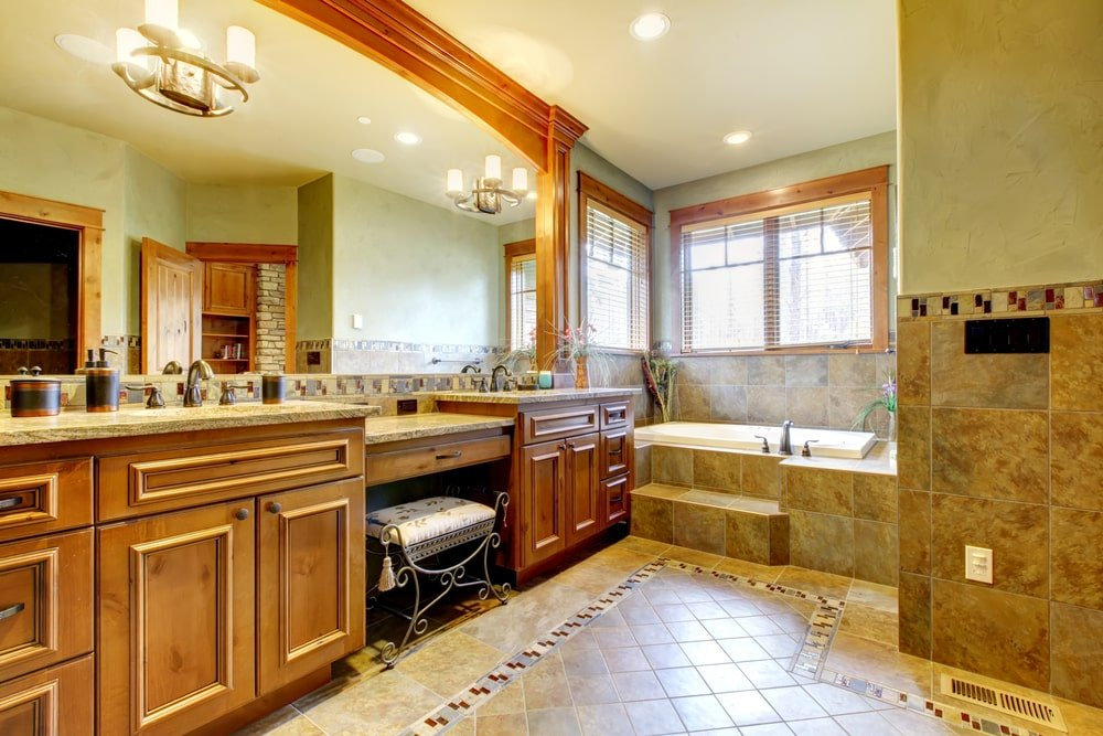 Warm primary bathroom with a deep soaking tub and dual sink vanity paired with a metal cushioned stool. It is illuminated by recessed lights and glass sconces mounted on the mirror.