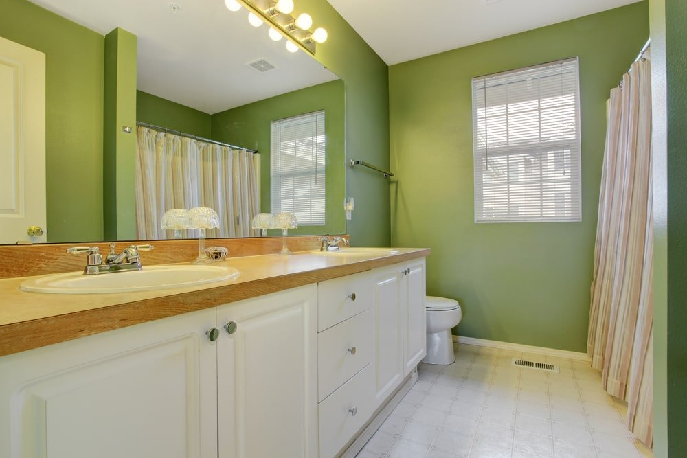 Green master bathroom with a toilet and white vanity that's topped with a light wood countertop and dual sink. There's a walk-in shower on the side enclosed in a striped curtain.