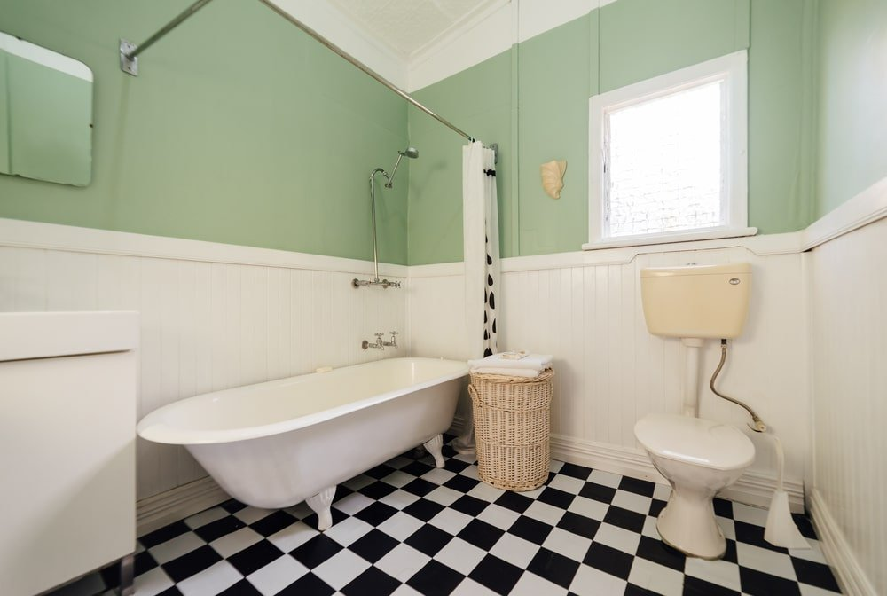 A rattan basket sits next to the tub and shower combo that's enclosed in a white curtain. It is accompanied by a sink vanity and a toilet over checkered flooring.