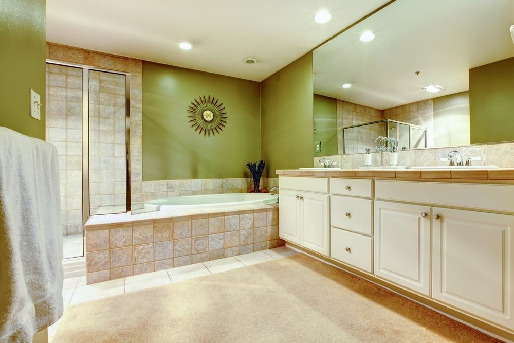 This master bathroom is decorated with a sunburst mirror that hung above the drop-in bathtub clad in beige tiles. It is situated in between the walk-in shower and white vanity with dual sink.