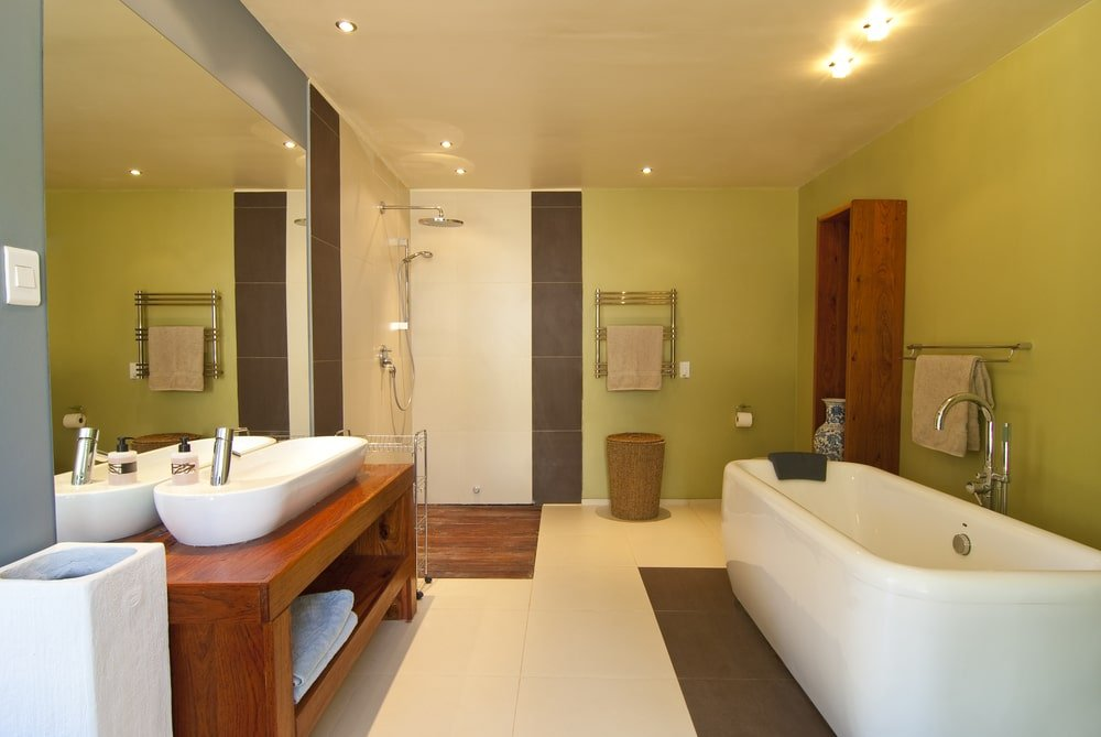 Green master bathroom with an open shower and a freestanding tub facing the wooden vanity that's topped with a vessel sink. It is illuminated by recessed lights fitted on the regular white ceiling.