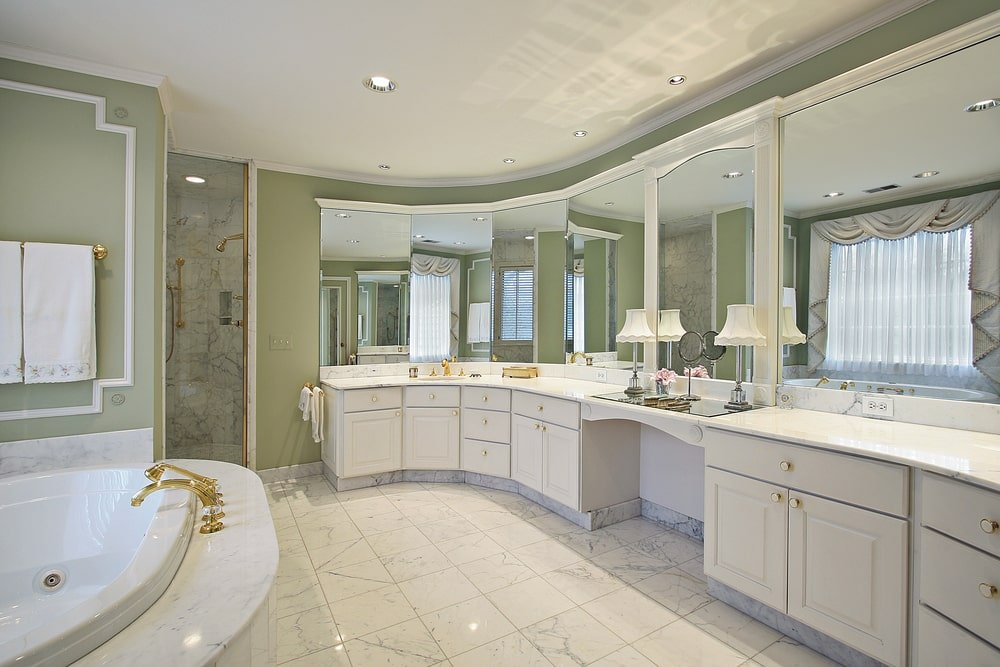 Luxury master bathroom with a deep soaking tub and white vanity accented with brass fixtures and knobs. It includes a walk-in shower with marble backsplash matching with the tiled flooring and bathtub surround.