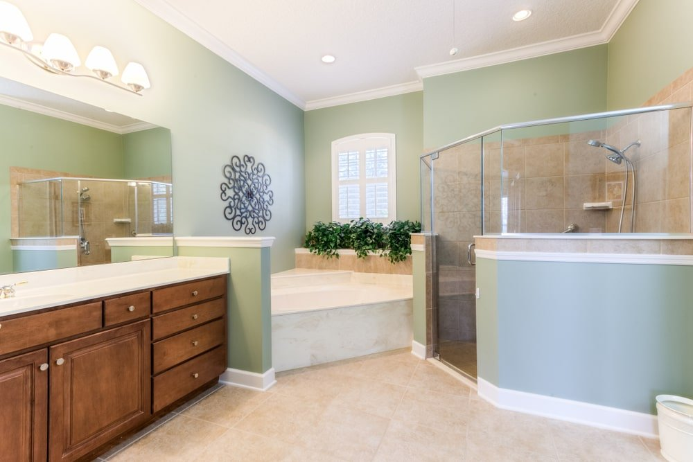 An ornate wrought iron wall art stands out against the sage green walls in this primary bathroom with a walk-in shower and a drop-in bathtub next to the wooden sink vanity with a quartz countertop.