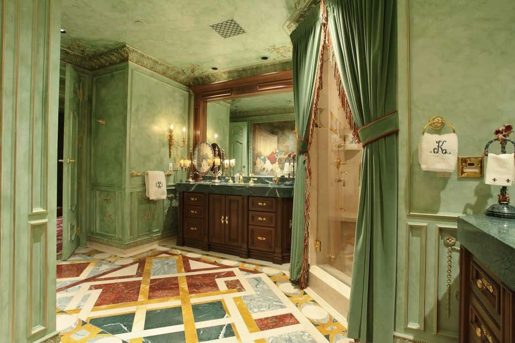 Dark wood vanities flank the walk-in shower that's dressed in lovely green curtains blending in with the wainscoted walls. It has multi-colored flooring and a regular ceiling lined with intricate crown molding.