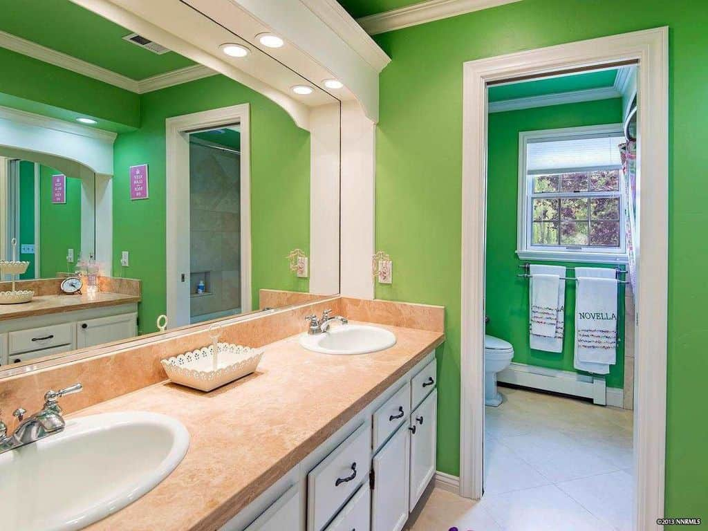 This primary bathroom showcases a toilet area and a white vanity topped with beige marble countertop and dual sink. It is paired with a large rectangular mirror that's illuminated by recessed lights.