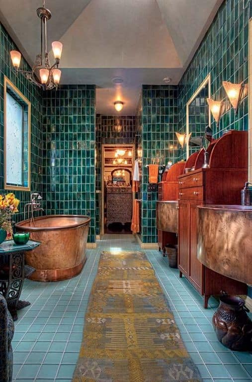 The eclectic primary bathroom features a copper freestanding tub along with his and her floating washstands paired with wooden cabinets. It has green tiled walls and flooring lined with a vintage runner.