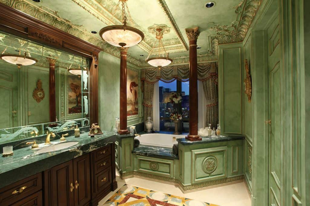 Deluxe master bathroom with green wainscoted walls and an intricate tray ceiling mounted with brass pendant lights. It includes a large vanity and an alcove tub lined with brown columns.