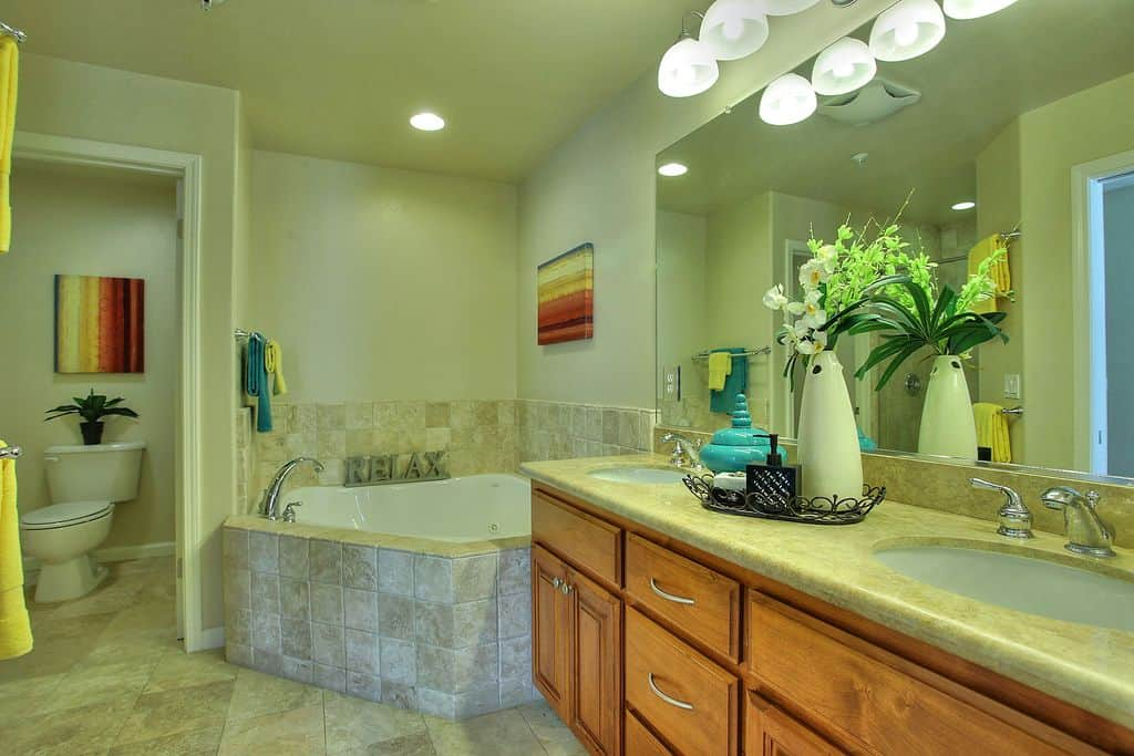Multi-colored paintings bring a pop of colors in this master bathroom with a toilet area and a corner tub situated next to the wooden vanity with dual sink and frameless mirror.