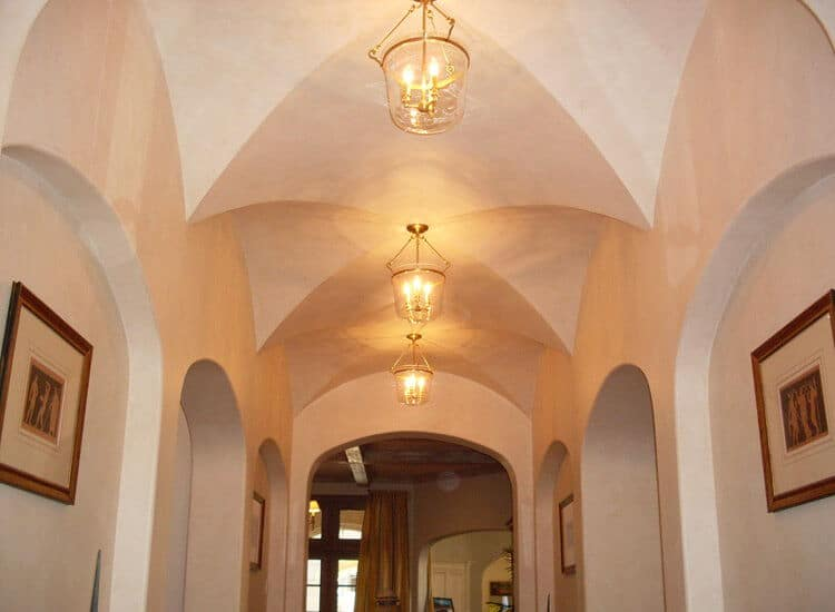 This is a narrow hallway within this charming home that has beige walls and a beautiful row of groin vaults on the long and narrow ceiling that is augmented by the warm yellow lights of the glass lantern pendant lights hanging from each middle point.
