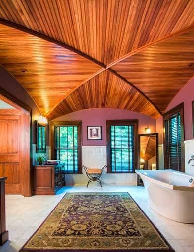 This charming master bathroom has a wooden plank ceiling with a groin vault shape. This wooden ceiling matches with the window frames as well as the wooden door. These are then contrasted by the bright white marble flooring and the white porcelain freestanding bathtub.