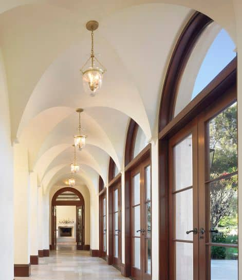 This long and narrow hallway that leads to the living room is lined with arched glass doors that bring in an abundance of natural lights to brighten the beige pillars connecting to groin vaults in the long and narrow ceiling of the same tone.