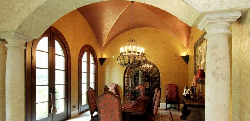 This elegant dining room has a classical vibe to its groin vault ceiling and the gorgeous decorative chandelier that brings a yellow amber glow to the beige ceiling together with the wall-mounted lamps on each corner. These provide a bright contrast for the dark tones of the dining set.