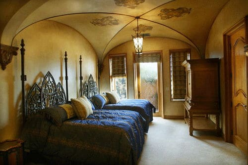 The two pencil poster beds both have intricate details on their headboard that stands out against the beige walls. These beige walls blend well with the beige groin vault ceiling adorned with lovely patterns on its four sides leading to the middle point where a lantern pendant light hangs.