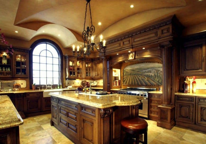 The wrought iron chandelier hanging over the kitchen island is supported by a beige groin vault ceiling with recessed lights matching the yellow lights of the chandelier to give this kitchen a warm glow as well as the wooden arch over the cooking area with a beautiful mural on its backsplash.