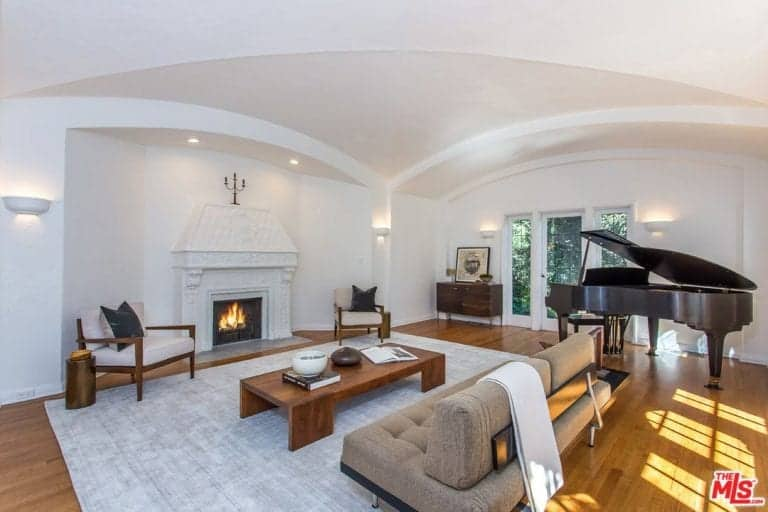 This bright and simple living room has uniform white walls, white mantle for the firplace and a white groin vault ceiling. These makes the black grand piano stand out as well as the various wooden furniture that is paired with the gray cushioned sofa.