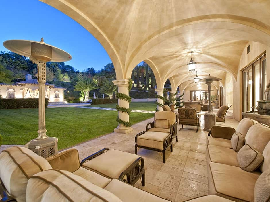 This beautiful patio at the back of the house has beige outdoor tiles that blend with the beige cushioned sofa set. These also matches with the beige pillars that are supporting the groin vaults of the long ceiling with lantern pendant lights on each middle point.