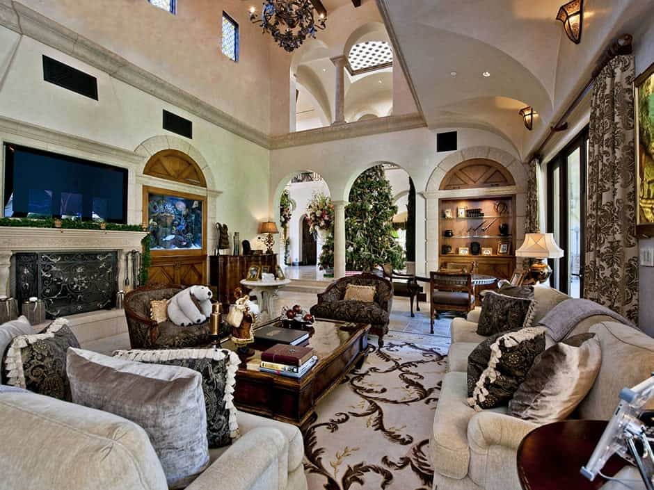 This is an elegant and luxurious living room with a high ceiling in the middle over the wooden coffee table to the fireplace. On the other side, the ceiling of the long beige couch is given a lower ceiling with groin vaults and wall-mounted lamps.