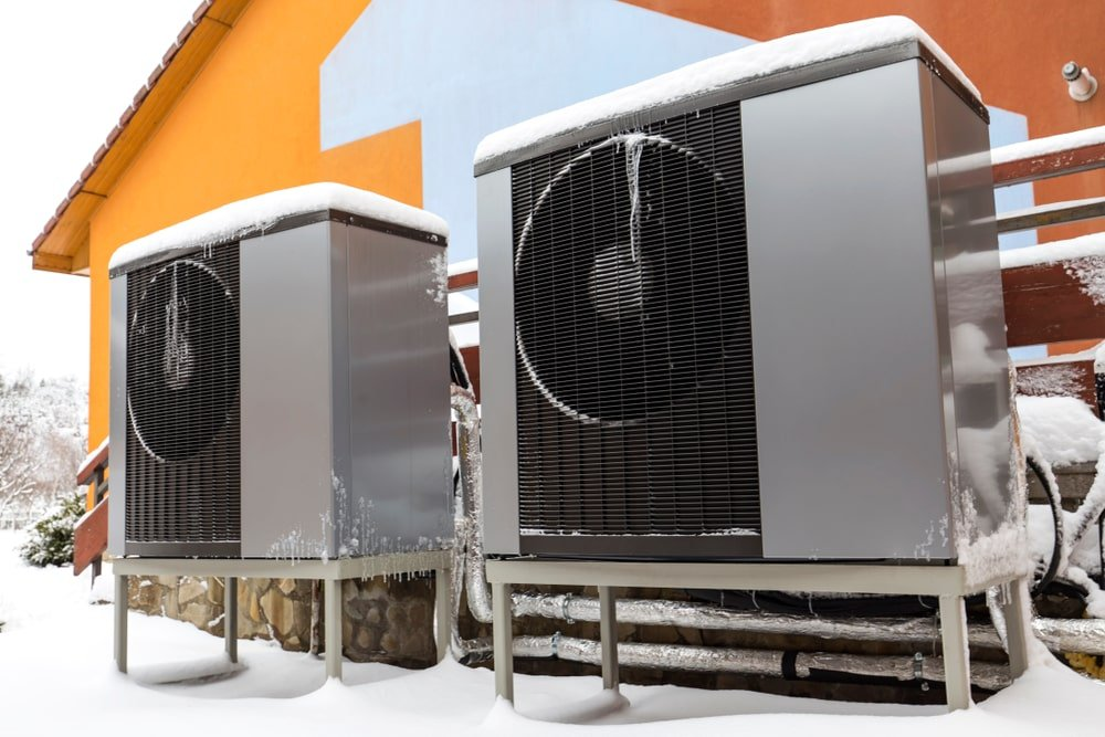 Modern heat pumps outside a home during winter.
