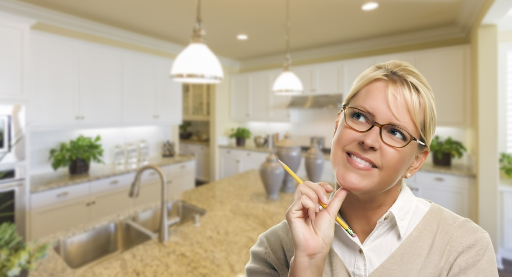 A woman looking thoughtfully while holding a pencil in the kitchen.