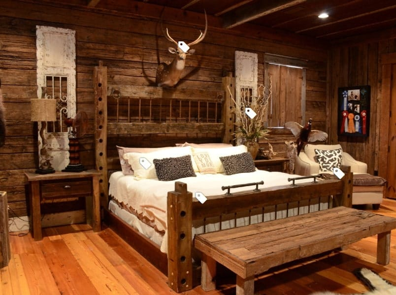 A focused shot at this primary bedroom's rustic walls and a ceiling, along with hardwood flooring. The room offers a large bed set with rustic bedside tables.