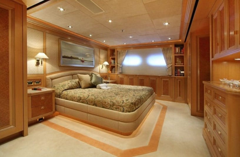 A primary bedroom boasting decorated carpet flooring and brown walls. The room has a large and extremely comfy bed along with cabinetry and built-in shelving.