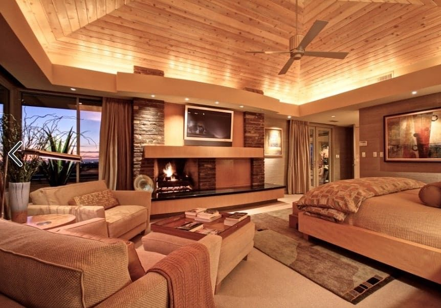 Large primary bedroom boasting brown walls, brown carpet floors and a brown wooden ceiling. The room offers a brown bed set and a fireplace, along with a sitting area on the side.
