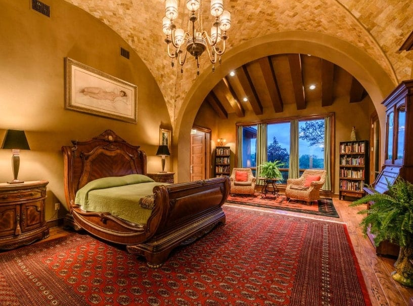 A spacious primary bedroom boasting a stunning bed set on top of a massive red area rug covering the hardwood flooring. The room has a stunning groin vault ceiling lighted by stylish chandelier.