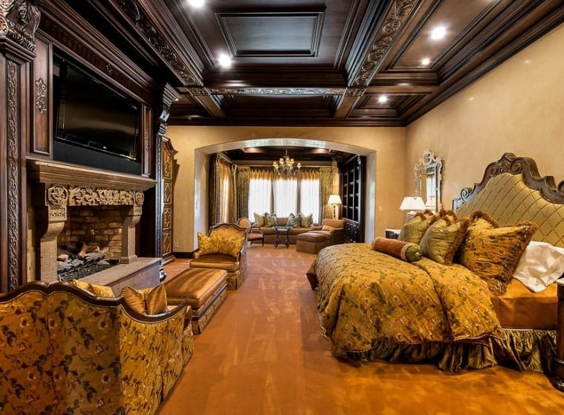 This primary bedroom boasts a stunning decorated ceiling and brown carpet flooring. The room offers a luxurious bed with a large widescreen TV set in front together with a fireplace featuring a sitting area nearby.