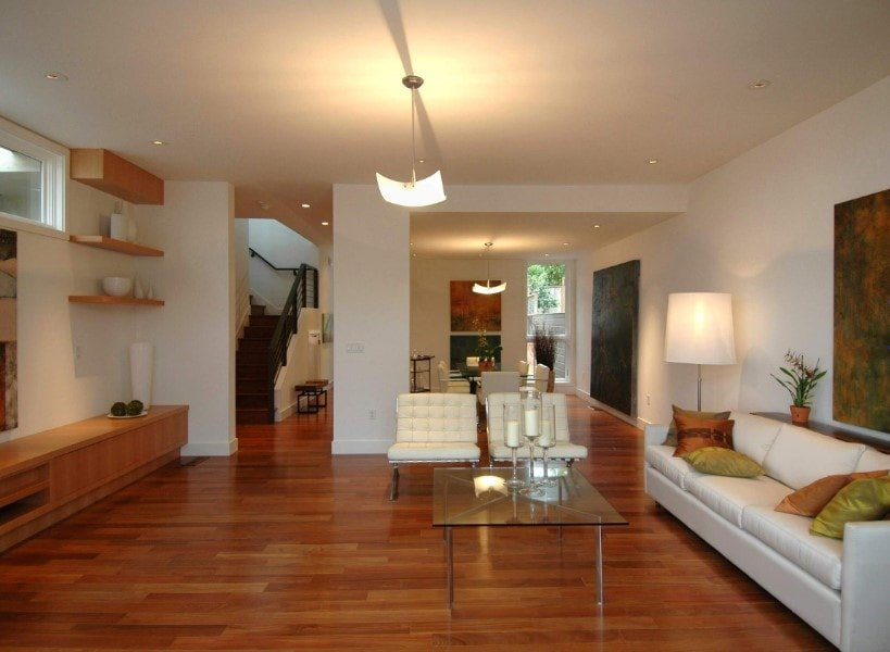 A spacious living space featuring hardwood flooring and a set of white seats, together with a glass top center table.