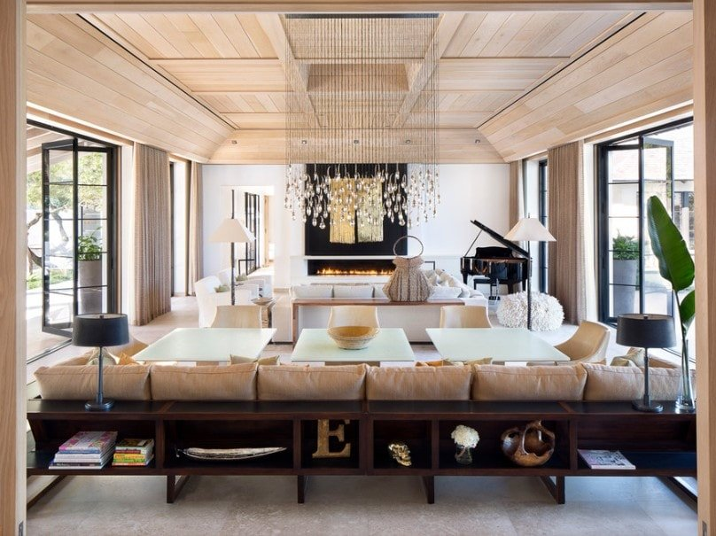 A stunning living room boasting a magnificent wooden tray ceiling along with elegant pieces of furniture. The ceiling lights are absolutely magnificent as well.