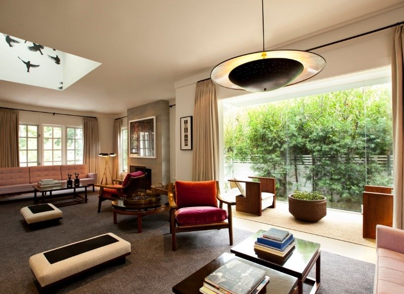 A spacious living room featuring classy and comfy seats on top of a large area rug. The ceiling offers a skylight and a pendant light.