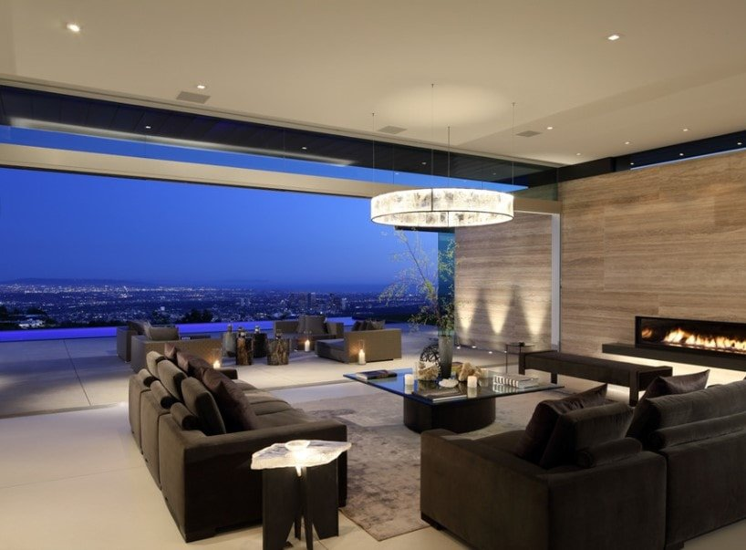 A contemporary home boasting a living room with modern and stylish sofa set with a glass top center table. This area offers a stunning view of the surroundings.