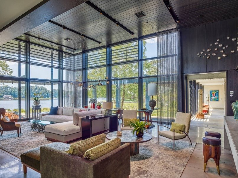 Large living room with a modern sofa set on top of a stylish area rug. The room features a custom ceiling and glass windows.