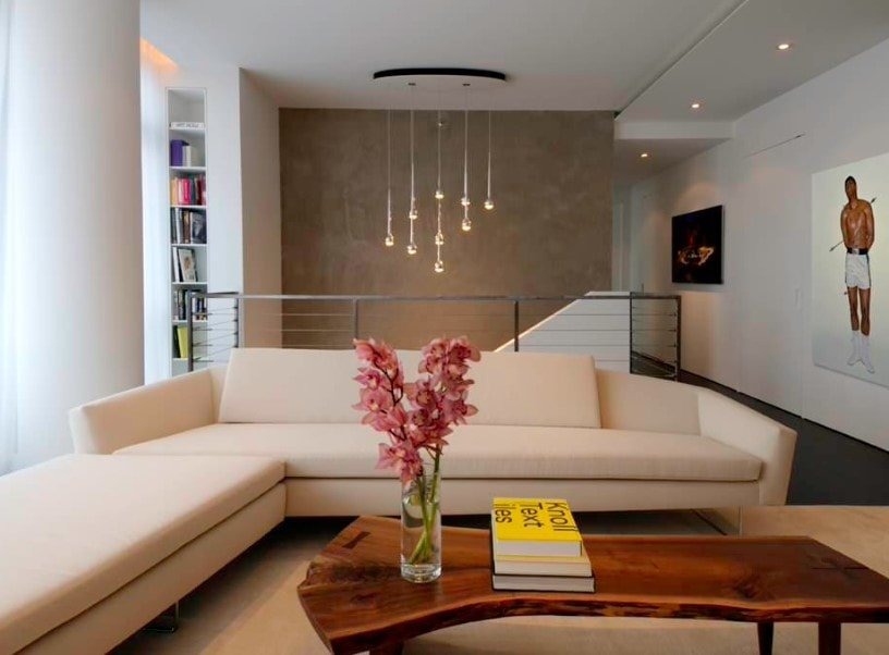A focused shot at this living room's modern L-shaped sofa together with the thick wooden center table.