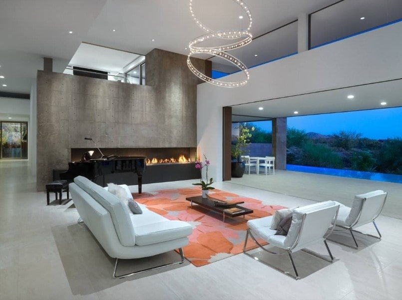 A contemporary house offering a modern living space with a white sofa set and a gorgeous ceiling light, together with an elegant black piano and a modern gas fireplace.