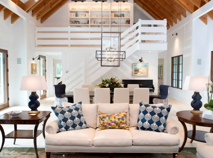 A great room featuring a classy sofa set in the living room along with a beautiful dining table and chairs set under the home's tall vaulted ceiling with exposed beams.